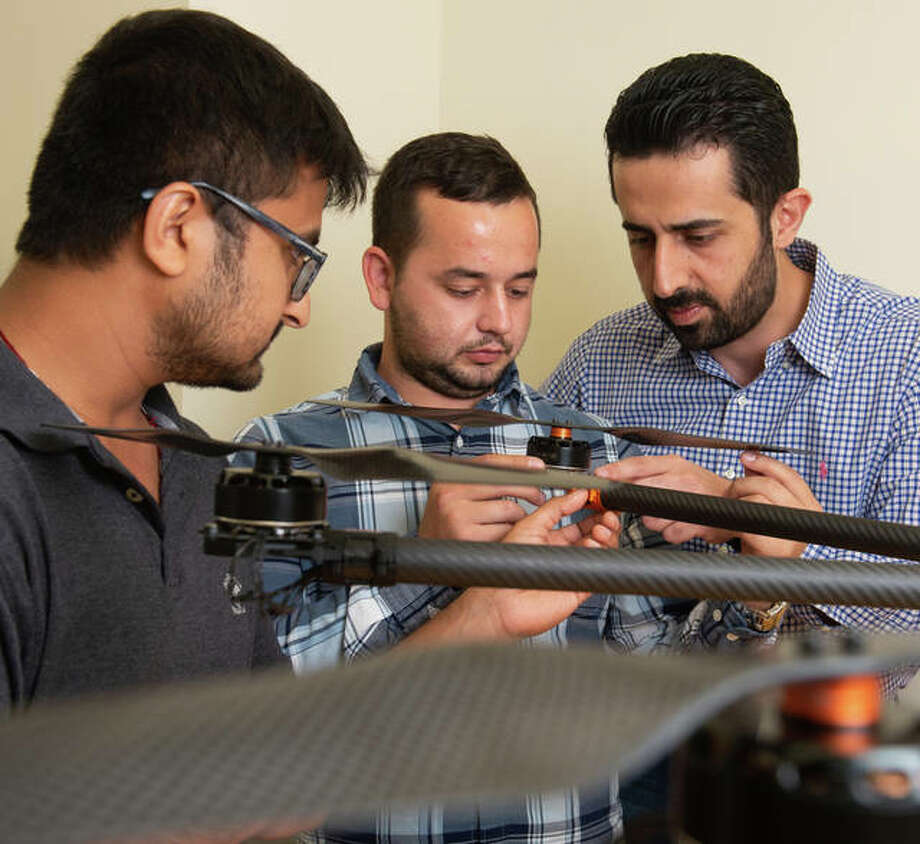 SIUE School of Engineering's Nima Lotfi, PhD, (back) and his students Nedret Ramic (middle), a mechanical engineering graduate student, and Pratik Lamsal, a senior mechanical engineering major, assemble a large drone. Photo: For The Telegraph