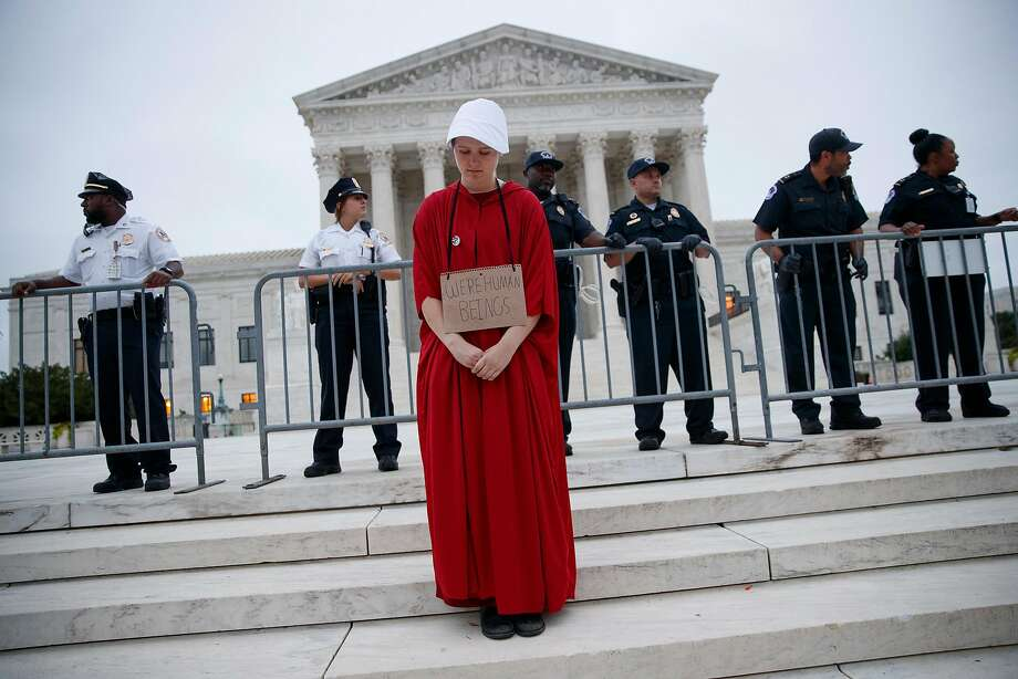"""A demonstrator dressed as a character from """"The Handmaid's Tale"""" protests Saturday at the Supreme Court in Washington. Photo: Tom Brenner / New York Times"""