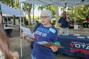 Lynn Dahlberg, volunteer deputy voter registrar with Mi Familia Vota, speaks with passersby Saturday about registering to vote at Miller Outdoor Theatre in Hermann Park in Houston.