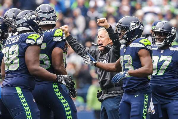 Seattle Seahawks Head Coach Pete Carroll celebrates an interception by defensive end Frank Clark against the L.A. Rams Sunday, Oct. 7, 2018.