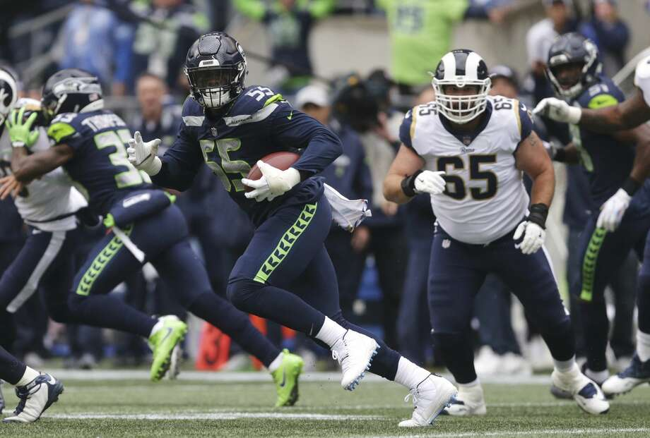 Seattle Seahawks defensive end Frank Clark (55) runs the ball after he intercepted a pass during the first half of an NFL football game against the Los Angeles Rams, Sunday, Oct. 7, 2018, in Seattle. (AP Photo/Scott Eklund) Photo: Scott Eklund/AP