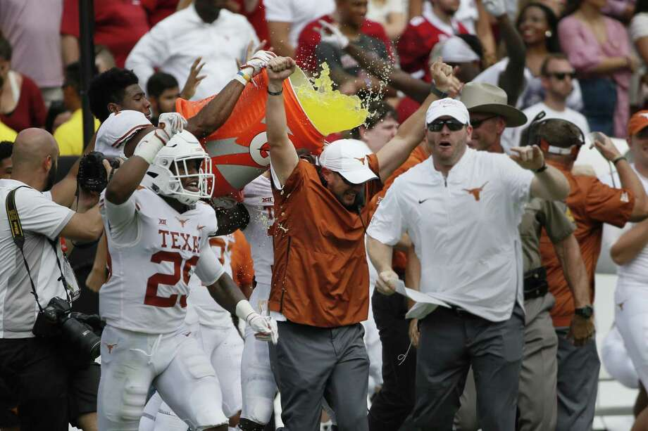 Texas Longhorns Head Coach Tom Herman (center in orange) celebrates just before being doused with liquid after an NCAA college football game against the Oklahoma Sooners, Saturday in Dallas, Texas. Photo: Roger Steinman, FRE / Associated Press / FR171255 AP