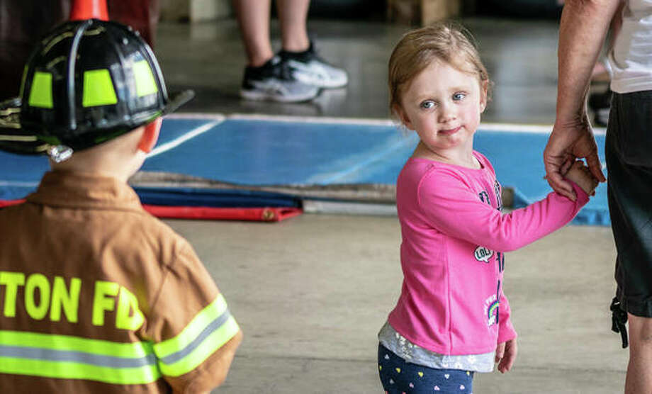One young girl admires the mini-uniform of perhaps a future Alton firefighter Sunday during Alton Fire Department's annual Open House. The day included several activities for children, including close-up looks of the department's fire trucks and ambulances. Photo: Nathan Woodside | The Telegraph