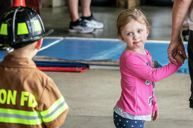 One young girl admires the mini-uniform of perhaps a future Alton firefighter Sunday during Alton Fire Department's annual Open House. The day included several activities for children, including close-up looks of the department's fire trucks and ambulances.
