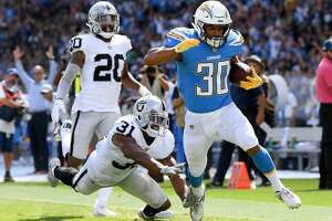 Austin Ekeler #30 of the Los Angeles Chargers beats Marcus Gilchrist #31 and Obi Melifonwu #20 of the Oakland Raiders to score a touchdown to take a 10-3 lead during the second quarter at StubHub Center on October 7, 2018 in Carson, California.