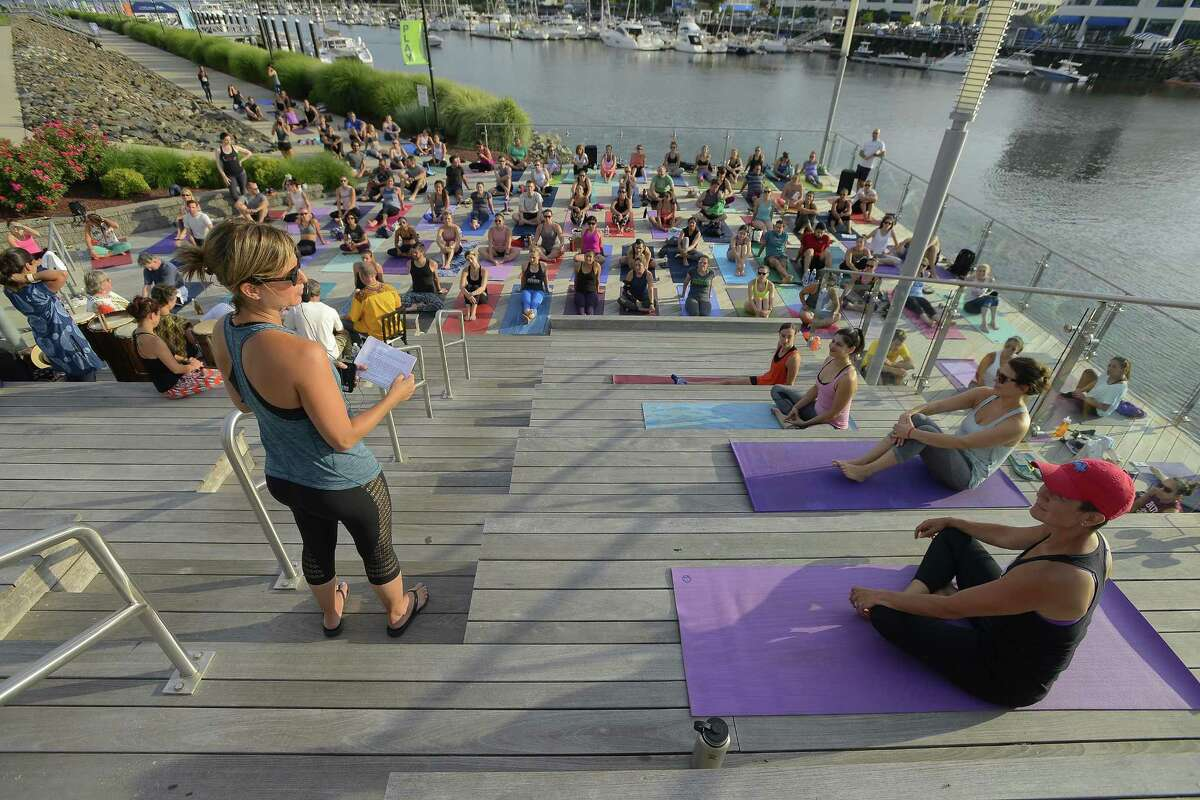 Aimee Elsner of Connecticut Power Yoga speaks at the 5th annual Yoga Jam 2017 at Harbor Point boardwalk in Stamford.