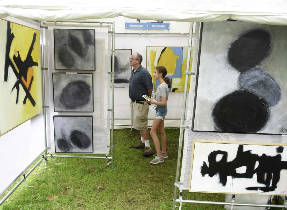 Old Greenwich's John Boyd and Stella Boyd, 12, look at work by Audrey Klotz at the 37th annual Bruce Museum Outdoor Arts Festival in Greenwich, Conn. Sunday, Oct. 7, 2018. The juried show is one of the top fine arts festivals nationally, attracting more than 85 new and returning artists from across the country in a variety of mediums. All works were available for purchase with artists on hand to discuss their pieces and process. The event also featured food trucks, free art activities for children and live music. Photo: Tyler Sizemore / Hearst Connecticut Media / Greenwich Time