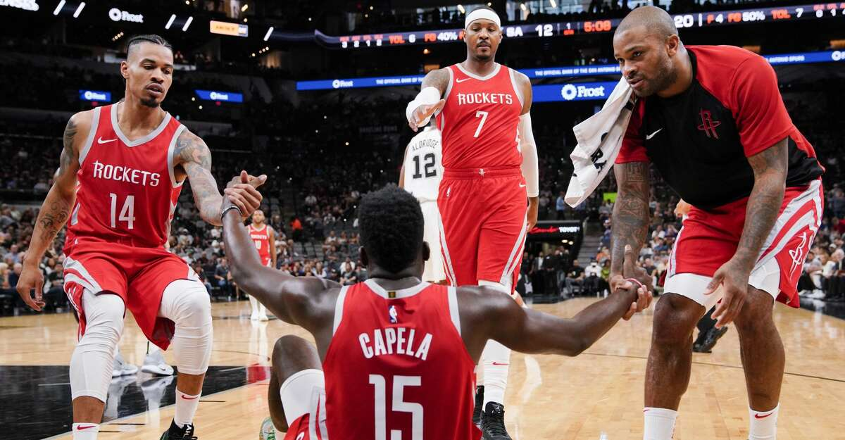 Houston Rockets' Clint Capela (15) is helped up by teammates Gerald Green (14), Carmelo Anthony (7), and P.J. Tucker during the second half of an NBA preseason basketball game against the San Antonio Spurs, Sunday, Oct. 7, 2018, in San Antonio. (AP Photo/Darren Abate)