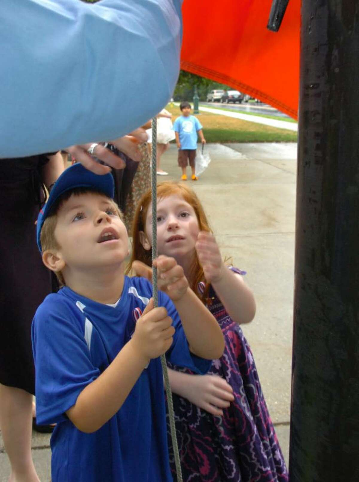 Brandon Lamouille, 6, left, and his sister Emma, 5, of Stamford, raise the French flag to celebrate Bastille Day in front of Greenwich Town Hall, on Wednesday, July 14, 2010.