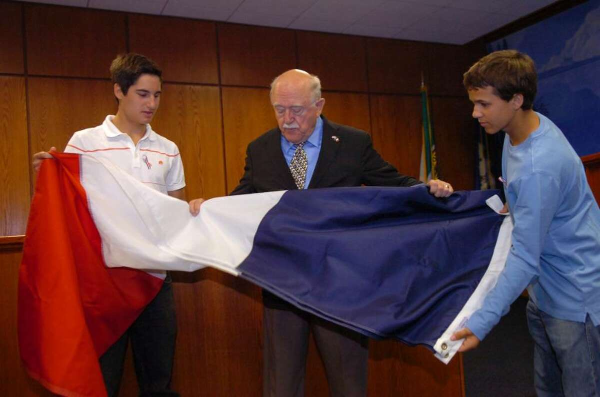 Serge Gabriel, of Greenwich, chairman of the town's Bastille Day celebration, with his grandsons, Hakan Karabey, 17, of New York, N.Y., left, and Michael Schobitz,16, of Munich, Germany, unfold the French flag in preparation to raise the flag at Town Hall, on Wednesday, July 14, 2010.