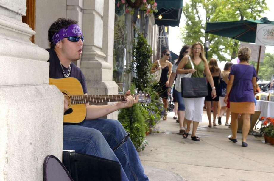 Zac Casey, of Greenwich, sings and plays the guitar during last summer's Sidewalk Sale Days in downtown Greenwich. This year's event runs from July 15-17. Photo: File Photo / Greenwich Time File Photo