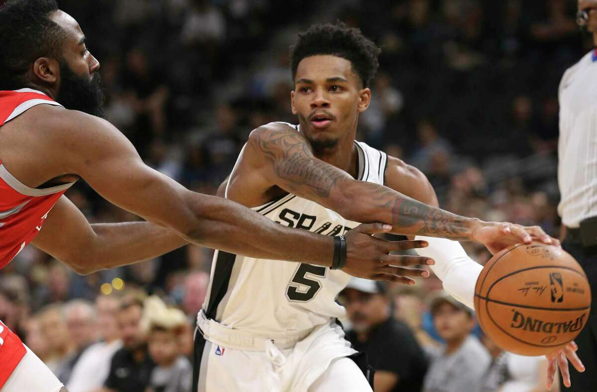 San Antonio Spurs' Dejounte Murray passes around Houston Rockets' James Harden during the first half at the AT&T Center, Sunday, Oct. 7, 2018.