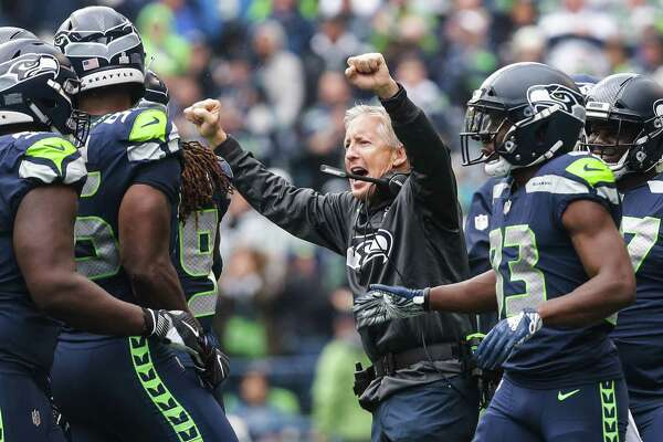 Seahawks coach Pete Carroll celebrates an interception by defensive end Frank Clark during the first half of the Seahawks game against the Los Angeles Rams, Sunday, Oct. 7, 2018 at CenturyLink Field.