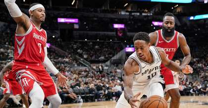 dc1033ceba69 San Antonio Spurs  DeMar DeRozan (10) tangles with Houston Rockets  Carmelo  Anthony (7) and James Harden during the second half of an NBA preseason ...