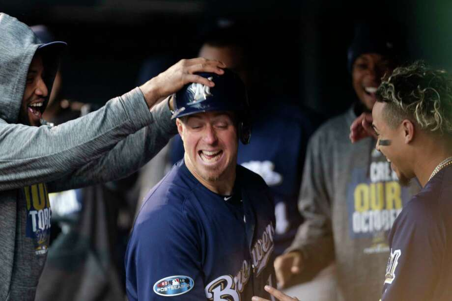 Teammates congratulate Milwaukee Brewers' Erik Kratz as he returns to the dugout after scoring on a wild pitch thrown by Colorado Rockies relief pitcher Scott Oberg in the sixth inning of Game 3 of a baseball National League Division Series Sunday, Oct. 7, 2018, in Denver. (AP Photo/Joe Mahoney) Photo: Joe Mahoney / Copyright 2018 The Associated Press. All rights reserved.