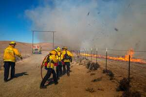 Fire fighters battle a wild land fire with wind gust blowing upwards of 50 mph, kicking up debris and burning over 4000 acres on ranch and preserve land near the Grizzly Island Wildlife Area, Sunday 07 October 2018 in Solano County, CA.