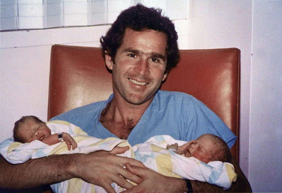 George W. Bush, seen here in a 1981 file photo in Dallas, holds his twin daughters, Barbara and Jenna.  Photo: AP / GEORGE BUSH PRESIDENTIAL LIBRARY