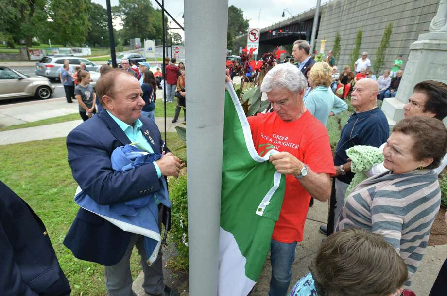 Walter Cerretani and and Tony DiCerto raise the Italian flag, the Tricolore, during a ceremony at the statue of Christopher Columbus at the Heritage Wall after marching down West Avenue in the Columbus Day Parade Sunday in Norwalk. A joint effort between the Italian American Police Society of Southern Connecticut, the Norwalk Sons and Daughters of Italy, the Knights of Columbus and the St. Ann Club of Norwalk, all were invited to the St. Ann Club after for a Sunday Mass and dinner at its headquarters on Hendricks Avenue. Photo: Alex Von Kleydorff / Hearst Connecticut Media / Norwalk Hour
