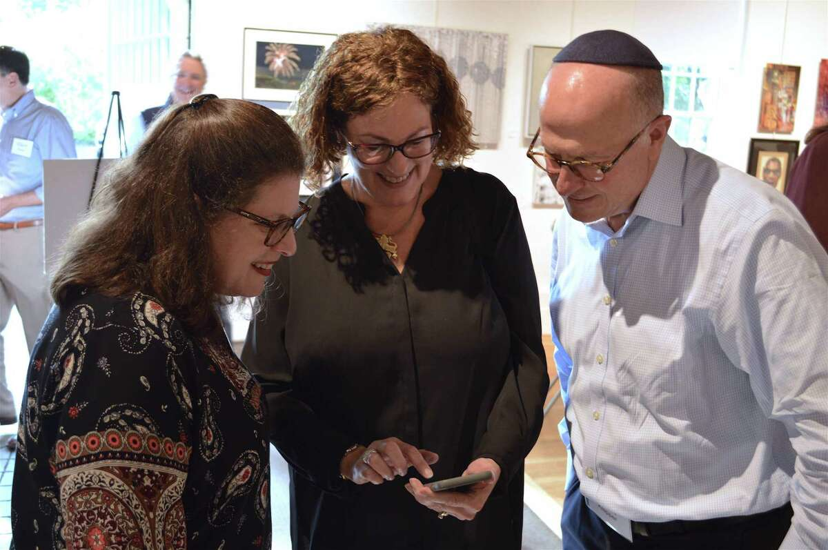 Nancy Mimoun, center, shares pictures with Elissa and Philip Klapper, all of Stamford, at the United Jewish Federation of Greater Stamford, New Canaan and Darien's Major Donor Reception at the Carriage Barn Art Center, Sunday, Oct. 7, 2018, in New Canaan, Conn.