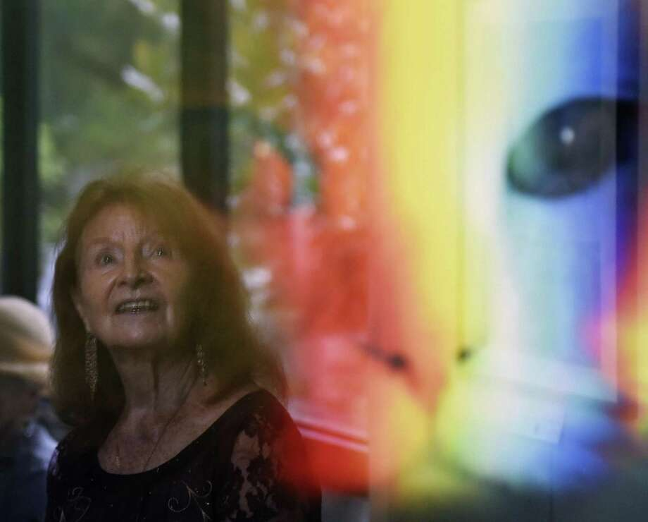 Old Greenwich resident Lucie Anderes is reflected in a photograph by Andrew Conner on display during the opening reception of the Art Society of Old Greenwich's Autumn Members Show at the Garden Education Center in the Cos Cob section of Greenwich, Conn. Sunday, Oct. 7, 2018. Works in a variety of mediums were presented at the show, judged by UConn Art & Art History Department Head John Richardson. The art will be on display until Oct. 28. Photo: Tyler Sizemore / Hearst Connecticut Media / Greenwich Time