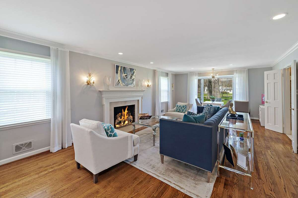 The spacious, front-to-back formal living room has a marble fireplace and bay window.