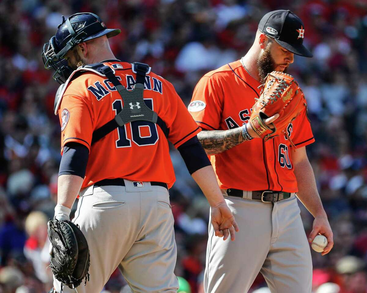 Houston Astros catcher Brian McCann (16) walks off the mound after talking to pitcher Dallas Keuchel (60) during Game 3 of the American League Division Series against the Cleveland Indians at Progressive Field on Monday, Oct. 8, 2018, in Cleveland.