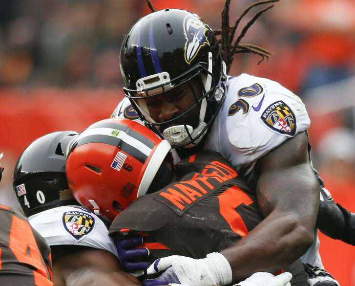 Baltimore Ravens linebacker Za'Darius Smith (90) and Kenny Young (40) sack Cleveland Browns quarterback Baker Mayfield (6) during overtime in an NFL football game, Sunday, Oct. 7, 2018, in Cleveland. (AP Photo/Ron Schwane)