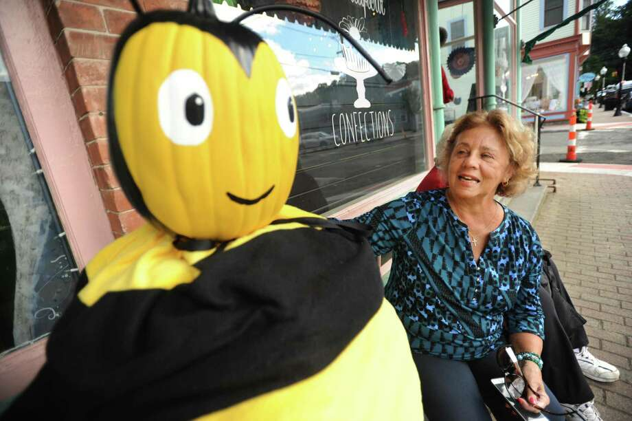 Judith Simpson, chairwoman of the Seymour Culture & Arts Commission, sits beside a bee scarecrow, one of 36 fanciful scarecrow creations decorating downtown Seymour. Photo: Brian A. Pounds / Hearst Connecticut Media / Connecticut Post