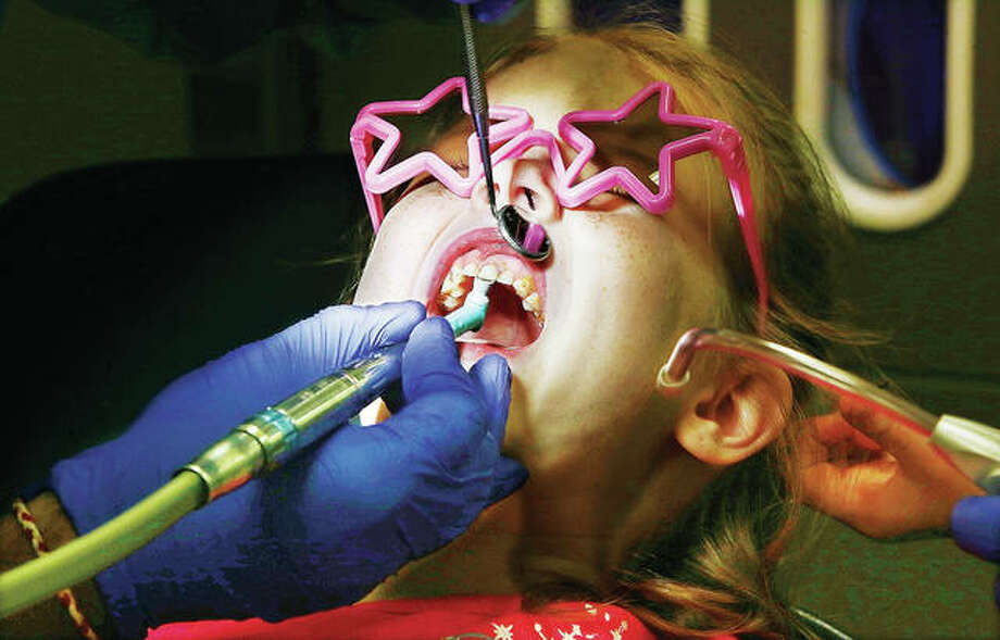 "Kaylynn, 6, may have looked uncomfortable Monday, but she was actually giggling most of the time as a cleaning and sealant were applied to her teeth and tickling her mouth at the SIU School of Dental Medicine clinic in Alton. Students Dushyant Patel and Claire Willenborg were doing the work as part of the dental school's annual ""Give Kids A Smile"" day at the clinic. Area school children, who missed no classes because of the Columbus Day holiday, were checked out and treated in a kid-friendly environment. Photo: John Badman 