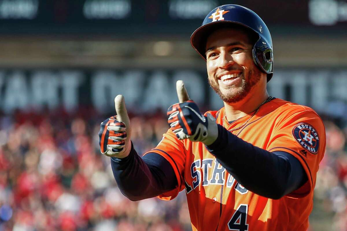 Houston Astros outfielder George Springer (4) gives a thumbs up after hitting a soft grounder for an infield single, moving Tony Kemp to third base, during the seventh inning of Game 3 of the American League Division Series against the Cleveland Indians at Progressive Field on Monday, Oct. 8, 2018, in Cleveland.