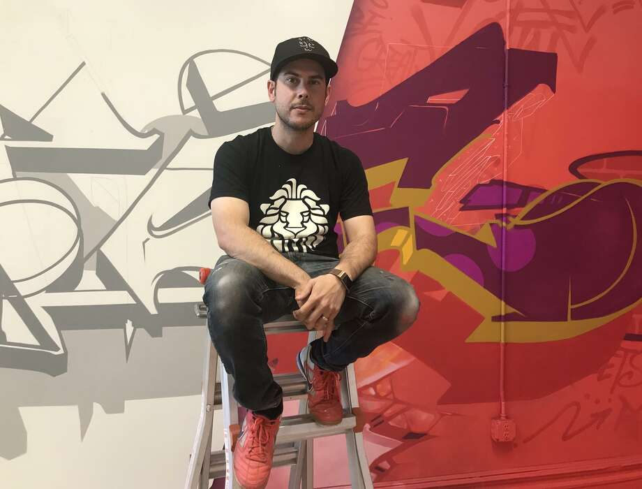 Graffiti artist Epic Uno of Old Greenwich poses with his latest work, which will be unveiled Thursday at Arts Alive! With the Greenwich Arts Council. Photo: Contributed Photo / Contributed / Greenwich Time Contributed