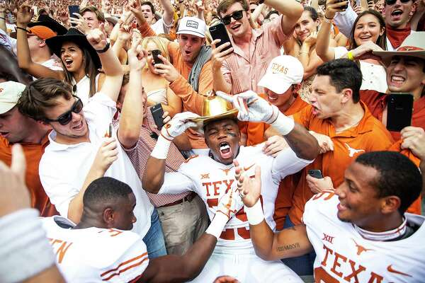Texas defensive back Josh Thompson (29) celebrates with fans while wearing the Golden Hat following Texas' 48-45 win over Oklahoma in an NCAA college football game at the Cotton Bowl, Saturday, Oct. 6, 2018, in Dallas. (Nick Wagner/Austin American-Statesman via AP)