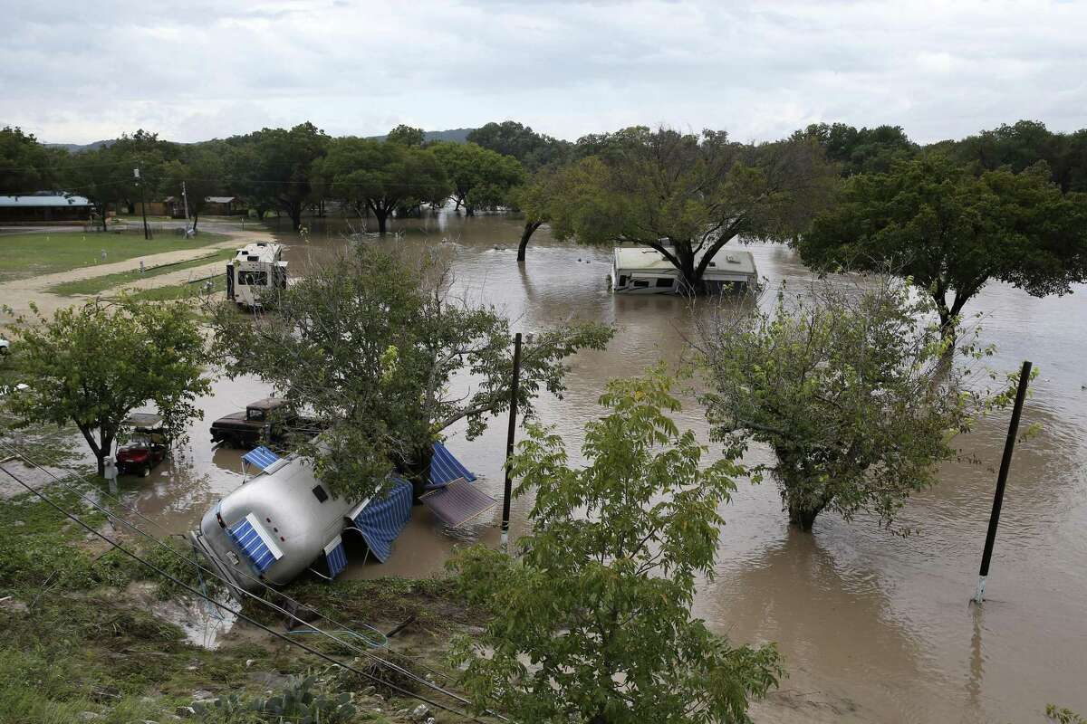 Recreation vehicles are seen strewn about at the South Llano River RV Park & Resort in Junction on Monday. Heavy rains the area caused the Llano River to flood and about 19 people were rescued. One woman swept away by floodwaters drifted more than 20 miles before she was rescued, according to the Texas A&M Forest Service.