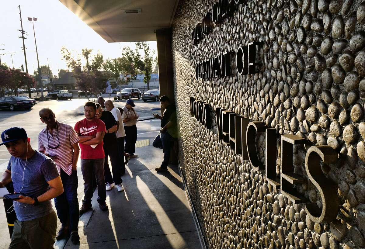FILE - In this Tuesday, Aug. 7, 2018, file photo, people line up at the California Department of Motor Vehicles prior to opening in the Van Nuys section of Los Angeles. California Gov.