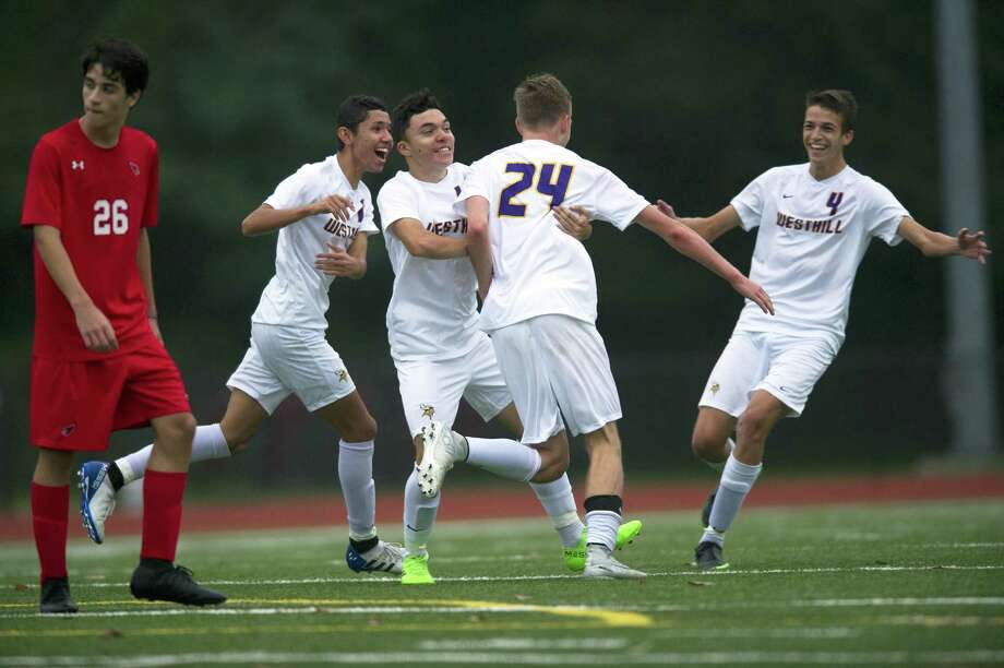 Westhill High School players, from left, David Torres, Jorge Betancour, Eric Zagaja and Christopher Matrullo joyously celebrate Zagaja's bicycle kick goal during a varsity boys soccer game against Greenwich High School at Cardinal Stadium in Greenwich, Conn. on Monday, Oct. 8, 2018. Greenwich and Westhill tied 2-2. Photo: Michael Cummo / Hearst Connecticut Media / Stamford Advocate