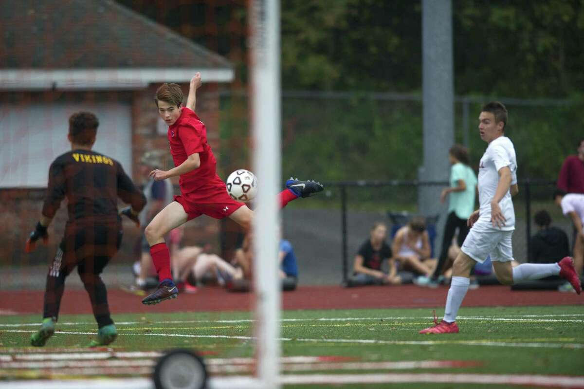 Greenwich High School junior Maxwell Pisacreta flies through the air as he sends a shot towards Westhill High School senior goalie Michael Leiva during a varsity boys soccer game at Cardinal Stadium in Greenwich, Conn. on Monday, Oct. 8, 2018. Greenwich and Westhill tied 2-2.