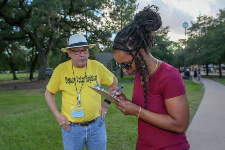 Miller Outdoor Theater visitor Lashandra Leonard fills out a voter registration form at Hermann Park in Houston.
