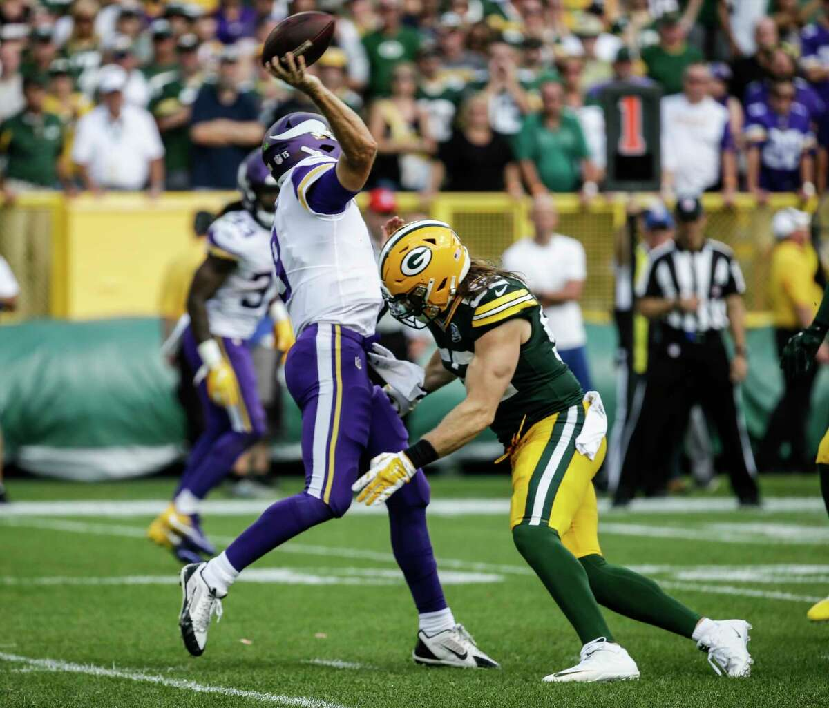 FILE - In this Sept. 16, 2018, file photo, Green Bay Packers?' Clay Matthews tackles Minnesota Vikings quarterback Kirk Cousins during the second half of an NFL football game, in Green Bay, Wis. Matthews was penalized for roughing the passer on the play. The NFL is getting roughed up over its amplified enforcement of roughing the passer penalties that has produced head-scratching, game-changing calls and a season-ending injury to a defender trying to comply with the league?'s mandate not to land on the quarterback. What constitutes a clean hit anymore is anyone's guess. (AP Photo/Mike Roemer, File)