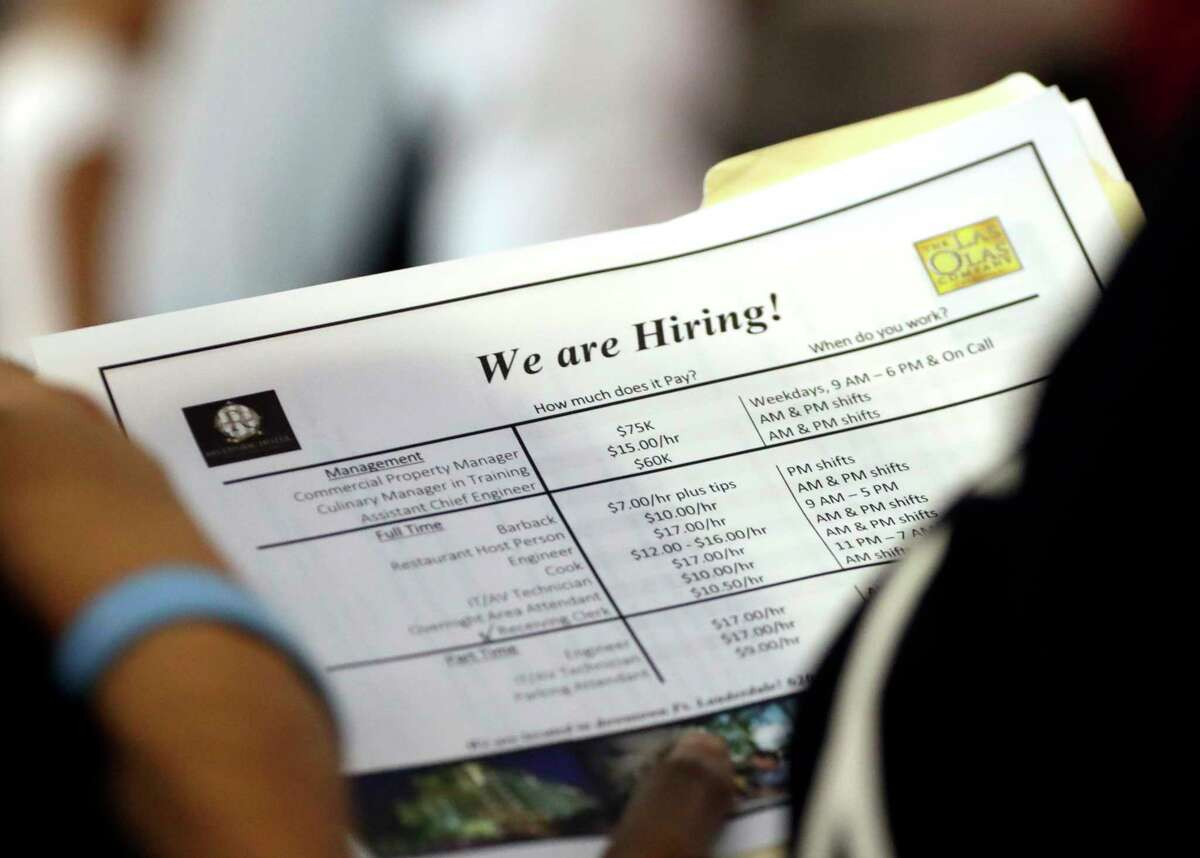 FILE In this June 21, 2018 file photo, a job applicant looks at job listings for the Riverside Hotel at a job fair hosted by Job News South Florida, in Sunrise, Fla. The U.S. unemployment rate fell to 3.7 percent in September 2018 the lowest level since December 1969 ?- signaling how the longest streak of hiring on record has put millions of Americans back to work. Employers added just 134,000 jobs last month, the fewest in a year, the Labor Department said Friday, Oct. 5. But that figure was likely depressed by the impact of Hurricane Florence. (AP Photo/Lynne Sladky)
