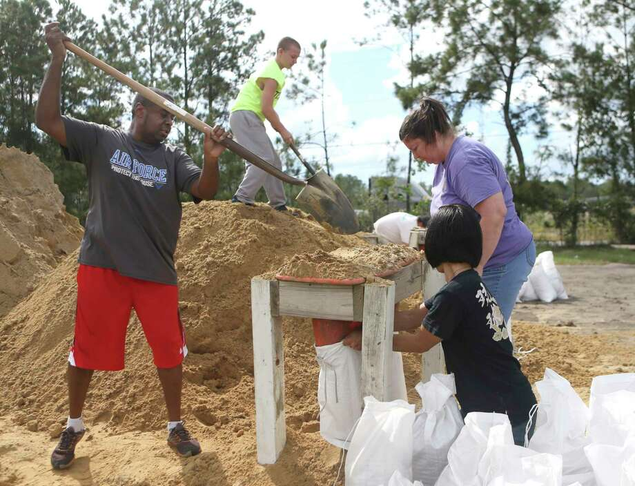 From left, Haskel Johnson, Daniel Tippett, Jennifer Tippett and Nobuko Johnson fill sand bags at the Lynn Haven Sports Complex in Lynn Haven, Fla., Monday, Oct. 8, 2018, to prepare for Hurricane Michael. (Patti Blake /News Herald via AP) Photo: Patti Blake / Patti Blake/The News Herald MANDATORY CREDIT