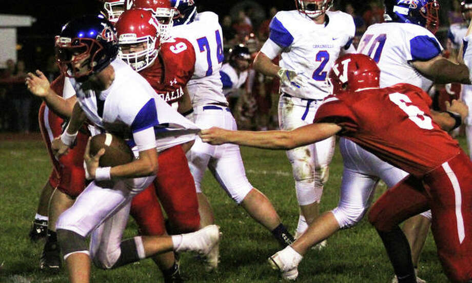 Carlinville quarterback Jarret Easterday (left) gets free from the grasp of Vandalia's Dustin Lott (6) on the way to the first of his four touchdown runs Friday night a Mark Greer Field in Vandalia. Photo: Greg Shashack / The Telegraph