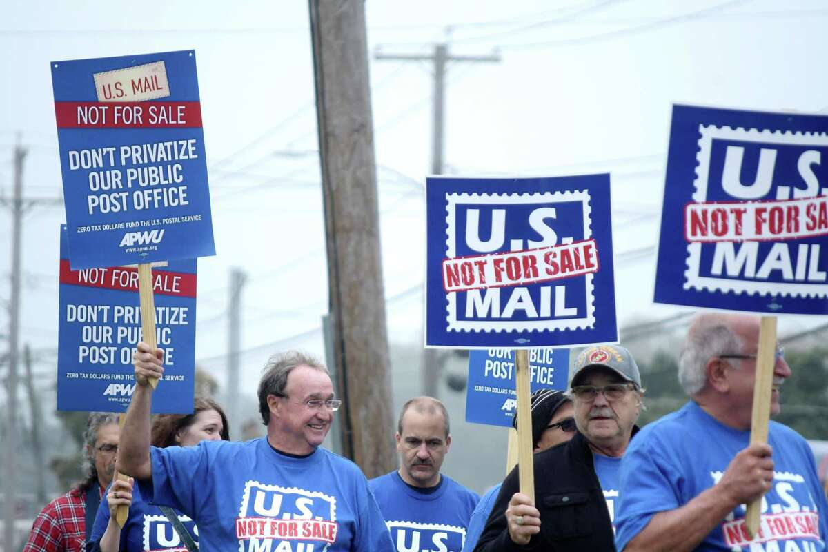 Members of the American Postal Workers Union, the National Association of Letter Carriers, and the National Postal Mail Handlers Union take part in a protest along Central Ave. to show their opposition to a Federal proposal to privatize the postal service, on Monday, Oct. 8, 2018, in Albany, N.Y. (Paul Buckowski/Times Union)