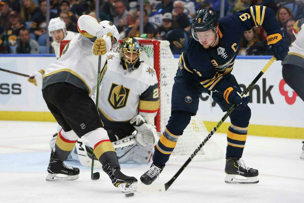 Buffalo Sabres forward Jack Eichel (15) passes the puck in front of Vegas Golden Knights goalie Marc-Andre Fleury (29) during the third period of an NHL hockey game, Monday, Oct. 8, 2018, in Buffalo N.Y. (AP Photo/Jeffrey T. Barnes)