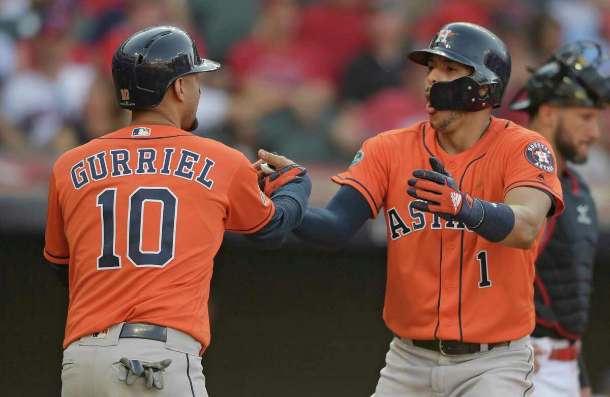 Houston Astros' Yuli Gurriel congratulates Carlos Correa after Correa hit a three-run home run in the eighth inning during Game 3 of a baseball American League Division Series against the Cleveland Indians, Monday, Oct. 8, 2018, in Cleveland. (AP Photo/David Dermer)