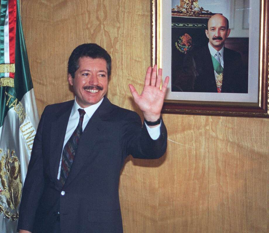 FILE--Secretary of Social Development Luis Donaldo Colosio greets reporters in his Mexico City office Nov. 28, 1993 after he was named as the ruling Institutional Revolutionary Party's presidential candidate. A Mexican flag and a portrait of Mexican President Carolos Salinas de Gortari are seen in the background. Special investigator Luis Raul Gonzalez of Mexico Attorney General's office gave his final report Friday, Oct. 20, 2000 on the March 26, 1994 assassination of then-presidential candidate Luis Colosio. The four-year investigation into the Tijuana killing of the PRI candidate concluded that he was killed by a lone gunman, Mario Aburto, now in prison. (AP Photo/Carolos Taboada) Photo: Carlos Taboada /AP / AP
