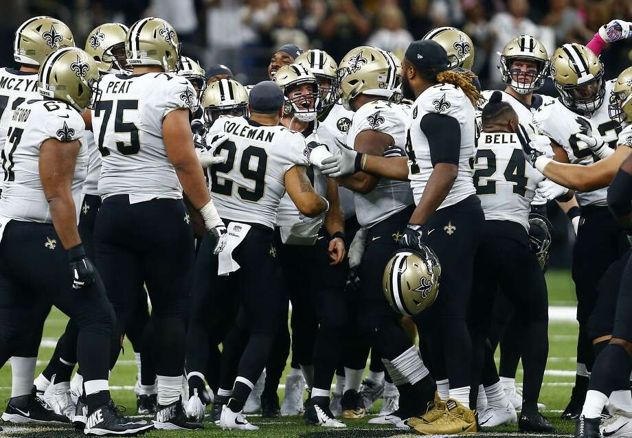 New Orleans Saints players surround Drew Brees after the quarterback broke the NFL all-time passing yards record. Photo: Butch Dill / Associated Press