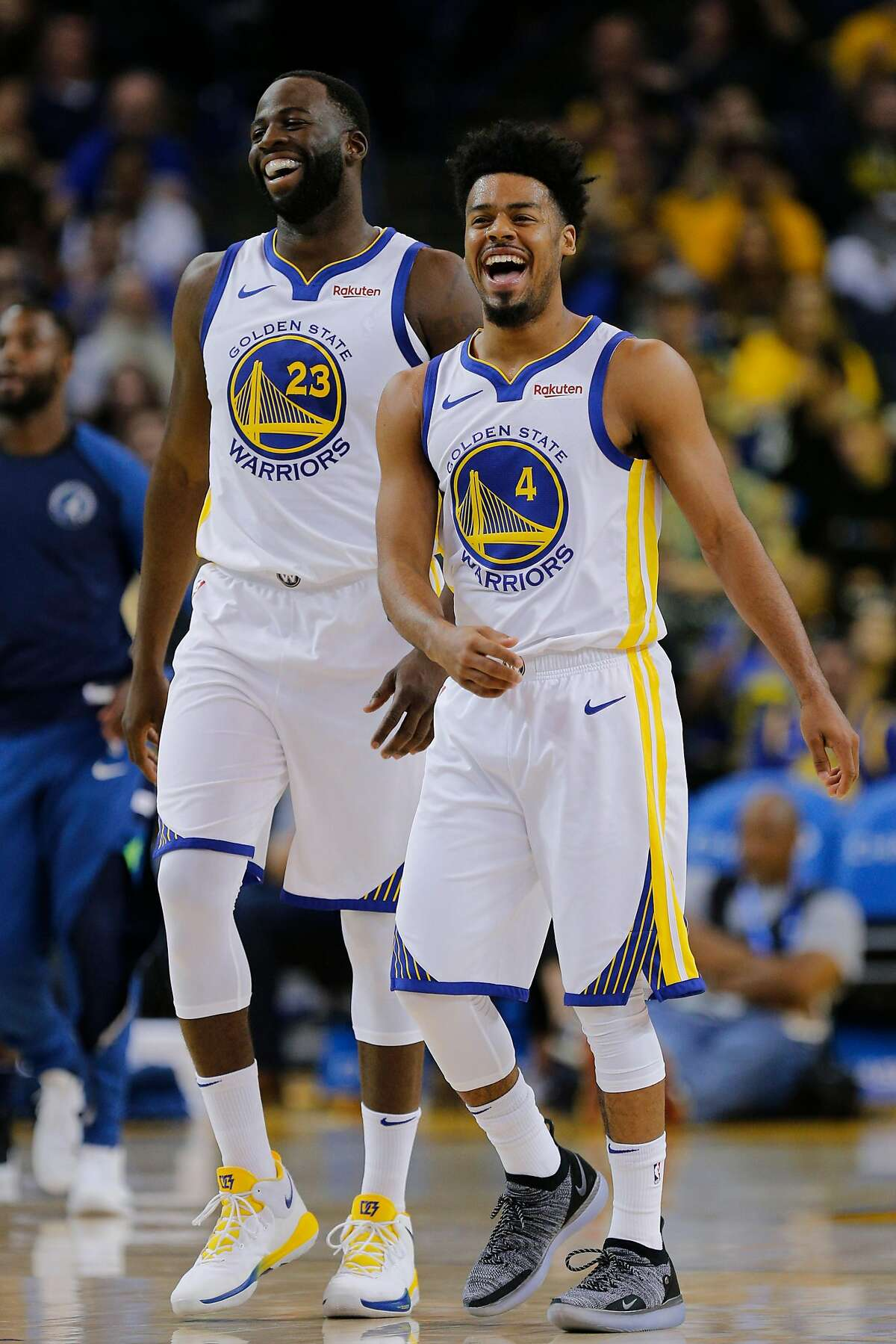 Golden State Warriors forward Draymond Green (23) and guard Quinn Cook (4) share a laugh at a timeout during the first half of an NBA preseason game between the Golden State Warriors and Minnesota Timberwolves at Oracle Arena on Saturday, Sept. 29, 2018, in Oakland, Calif.