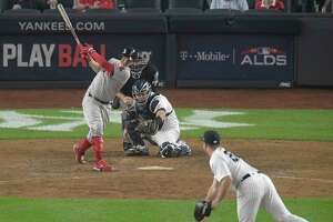 Boston Red Sox's Brock Holt connects for a two-run home run against New York Yankees' Austin Romine (28) during the ninth inning of Game 3 of baseball's American League Division Series, Monday, Oct. 8, 2018, in New York. (AP Photo/Bill Kostroun)