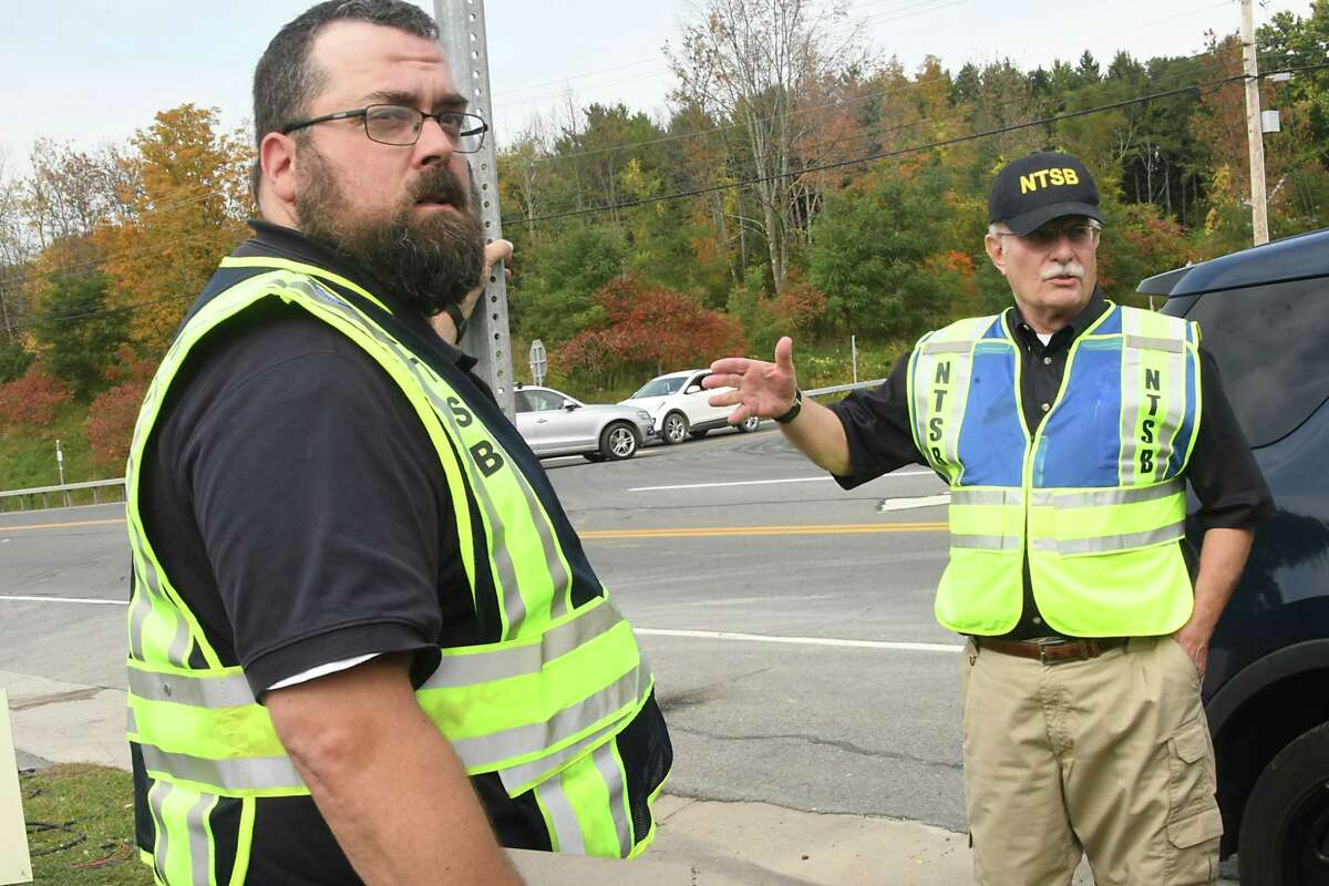 Dennis Collins, left, and Michael Lapont, both of the National Transportation Safety Board, discuss clearing the media away from the scene where the limousine and pedestrian accident took place that killed 20 people Saturday near the Apple Barrel Country Store at Routes 30 and 30A on Monday, Oct. 8, 2018 in Schoharie, N.Y. They were planning on putting a drone in the air to survey from above. (Lori Van Buren/Times Union)
