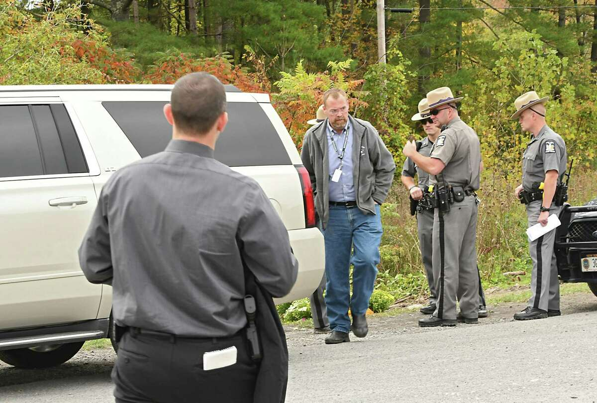 State Police are seen talking behind a coroner's car at the scene where the limousine and pedestrian accident took place that killed 20 people Saturday near the Apple Barrel Country Store at Routes 30 and 30A on Monday, Oct. 8, 2018 in Schoharie, N.Y. (Lori Van Buren/Times Union)